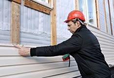 Un trabajador instala el apartadero beige de los paneles en la fachada Imágenes de archivo libres de regalías