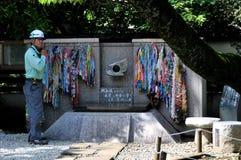 Un trabajador japonés se está colocando al lado del monumento de la paz de CND en el parque de Ueno en Tokio imágenes de archivo libres de regalías