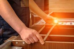 Un trabajador joven está montando los muebles de madera modernos de la cocina imagen de archivo libre de regalías