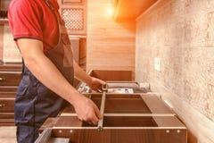 Un trabajador joven est? montando los muebles de madera modernos de la cocina fotos de archivo