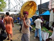 Un trabajador lleva una cesta en su cabeza Imagen de archivo