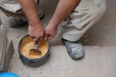 Un trabajador mezcla la lechada mano-seca del cemento en color del merengue con agua usando una paleta Para llenar los huecos ent imagen de archivo libre de regalías