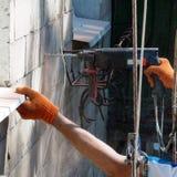 Un trabajador perfora la pared del edificio de varios pisos con un taladro eléctrico Imagen de archivo
