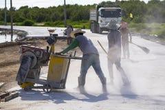 Un trabajador que corta el camino concreto con la máquina de la hoja de sierra del diamante Fotos de archivo