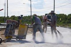 Un trabajador que cortaba el camino concreto con el diamante vio Imagenes de archivo