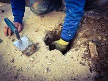 Un trabajador que lo alcanza en un agujero ` s que cava para sacar la tierra y los escombros Imágenes de archivo libres de regalías