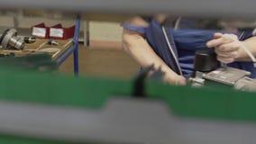 Un trabajador recoge una parte en una empresa industrial Primer de manos en el movimiento de detrás el soporte almacen de video