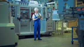 Un trabajador se está colocando en el medio de una unidad de la fábrica con una tableta almacen de metraje de vídeo