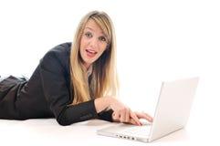 Un trabajo de la chica joven sobre la computadora portátil aislada en blanco Foto de archivo libre de regalías