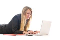 Un trabajo de la chica joven sobre la computadora portátil aislada en blanco Fotografía de archivo