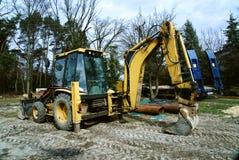 Un trabajo que espera del excavador amarillo para imagen de archivo