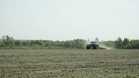 Un tracteur avec un cultivateur fonctionne le sol pour la plantation banque de vidéos