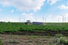 Un tracteur avec des tours d'une remorque par le champ sur le fond des turbines de vent photos stock