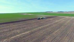 Un tracteur conduit sur un champ banque de vidéos