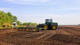 Un tracteur cultivant un champ Images stock