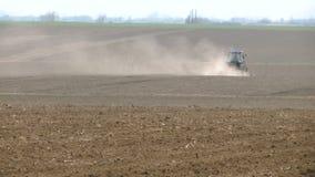 Un tracteur dans un domaine avec un nuage de poussière derrière lui clips vidéos