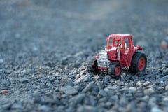 Un tracteur de jouet sur le sol rocheux photos stock