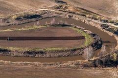 Un tracteur labourant un champ de ferme Photographie stock