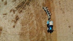 Un tractor azul con cuatro rejas de arado ara la tierra fértil seca del color marrón El concepto de cultivo, agricultura almacen de video