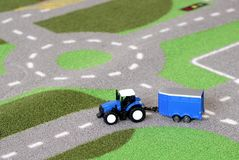 Un tractor azul del juguete del ` s del niño en una alfombra de la estera del camino Fotos de archivo