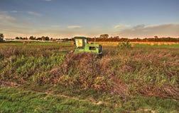 Un tractor en descanso, balas de heno en el fondo Fotografía de archivo