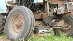 Un tractor oxidado viejo se coloca cerca del campo La máquina para la agricultura está esperando el proceso del campo almacen de video