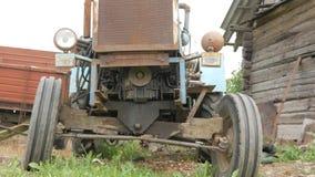 Un tractor oxidado viejo se coloca cerca del campo La máquina para la agricultura está esperando el proceso del campo metrajes
