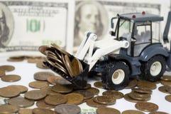 Un tractor que rastrilla monedas financiero Imágenes de archivo libres de regalías