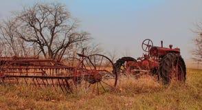Un tractor rústico viejo en un campo atado a una paleta Fotos de archivo libres de regalías