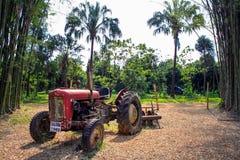 Un tractor rojo en las tierras de labrantío Imagen de archivo libre de regalías