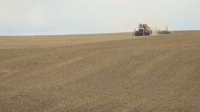 Un tractor siembra el campo arado usando una sembradora almacen de metraje de vídeo