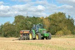 Un tractor verde con una semilla perfora adentro un campo de rastrojo Foto de archivo