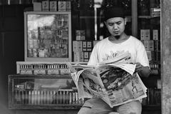 Un traficante que leía un libro delante de su tienda fotografía de archivo libre de regalías