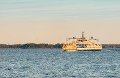 Un traghetto del veicolo attraversa l'open water al tramonto immagini stock