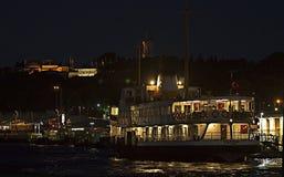 """Un traghetto pubblico chiamato """"Vapur """"al porto di Eminonu sotto il palazzo di Topkapi dell'impero ottomano di notte fotografie stock libere da diritti"""
