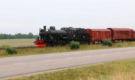 Un train de fret de vapeur près d'une route Images stock