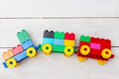Un train de jouet des cubes de lego sur un fond en bois Configuration plate Images stock