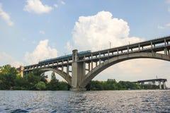 Un train monte au-dessus d'un pont au-dessus d'une rivière contre un ciel bleu Photos stock