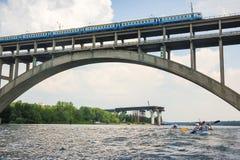 Un train monte au-dessus d'un pont au-dessus d'une rivière contre un ciel bleu Images libres de droits