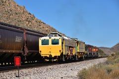 Un train se déplace le long d'une voie tandis que deux voitures jaunes reposent le ralenti Photo stock