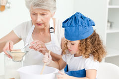 Un traitement au four de petite fille avec sa grand-mère image stock