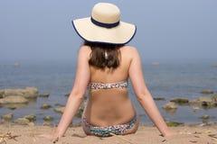 Un traje de natación de la mujer y un sombrero de paja que llevaban dieron vuelta con un trasero, la sentada en la arena y la mir Fotografía de archivo