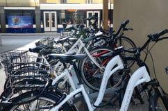 Un tram passe à côté des bicyclettes garées le long d'une rue à Genève photos stock