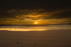 Un tramonto arancio su una spiaggia nelle isole di Orkney Immagine Stock