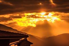 Un tramonto delle nuvole minacciose non impedisce il sole andare Immagine Stock