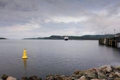 Un transbordador que se acerca a un puerto en la costa de Escocia en un día de veranos frío fotografía de archivo
