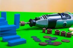Un trapano grigio con alcuni accessori di perforazione con i piccoli pezzi di legno blu su un fondo verde Immagini Stock Libere da Diritti