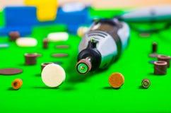 Un trapano grigio con alcuni accessori di perforazione su fondo verde Fotografia Stock Libera da Diritti