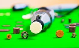 Un trapano grigio con alcuni accessori di perforazione su fondo verde Fotografie Stock Libere da Diritti