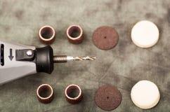 Un trapano grigio con gli accessori di perforazione su fondo grigio, sopra la vista Fotografie Stock Libere da Diritti